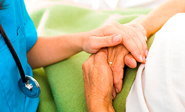 nurse holding the hand of an elderly patient