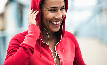 Hooded woman wearing headphones in a red jacket smiling
