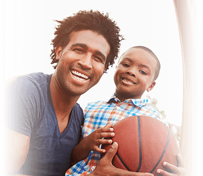 young father plays basketball with his son